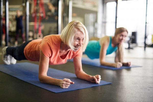 Mature blonde active woman standing in plank on mat during workout in contemporary fitness center